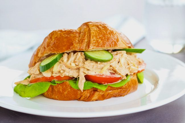 Spicy Asian-Cajun Chicken Salad Croissandwich made with tomatoes, butter lettuce, cucumber slices on top of a white plate on a chalkboard backdrop. Glass of sparkling water in the back.