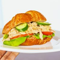 Hand holding up a white plate with a Spicy Asian-Cajun Chicken Salad Croissandwich made with tomatoes, butter lettuce, cucumber slices over a chalkboard backdrop.