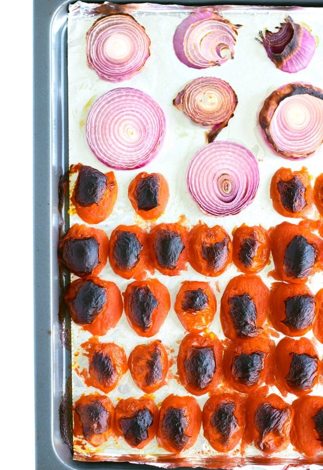Roasted and blackened roma tomatoes and red onion rings on top of a foil lined baking tray.