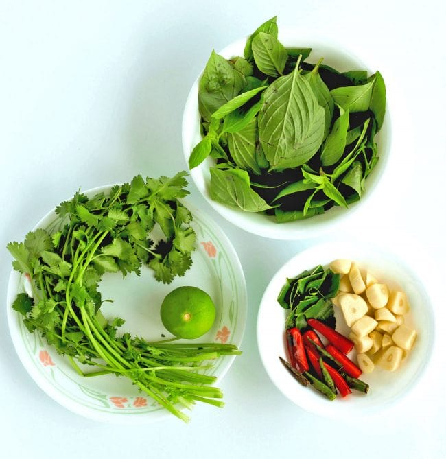 Bowl with Thai Sweet Basil Leaves, bowl with coriander and a lime, and a bowl with torn up kaffir lime leaves, garlic cloves, and roasted halved red and green chilies.