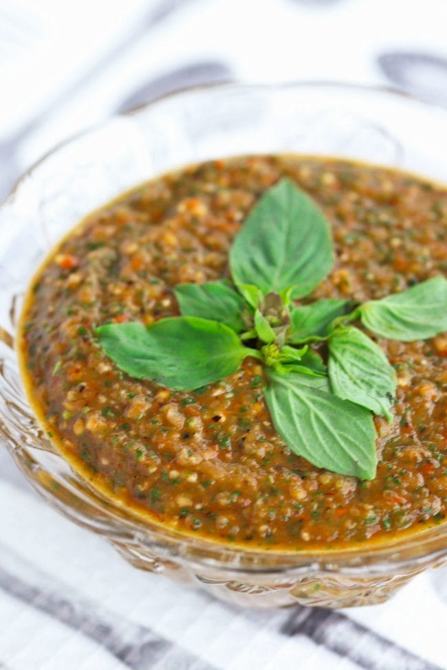 Small glass serving bowl with Thai Sweet Basil Roasted Tomato Salsa garnished with basil leaves on top of a white and gray utensil patterned napkin.