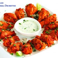 A white square plate of chicken tikka drumettes over a bed of chargrilled onion rings. Garnished with freshly chopped coriander. Lime wedges in the corners of the plate and in the center is a small dipping dish with cucumber and mint yogurt dip.