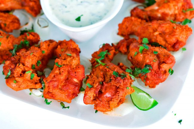 Close up of corner of square plate loaded with oven grilled chicken tikka drumettes and a small dish of cucumber and mint yogurt dip in the center of the plate.