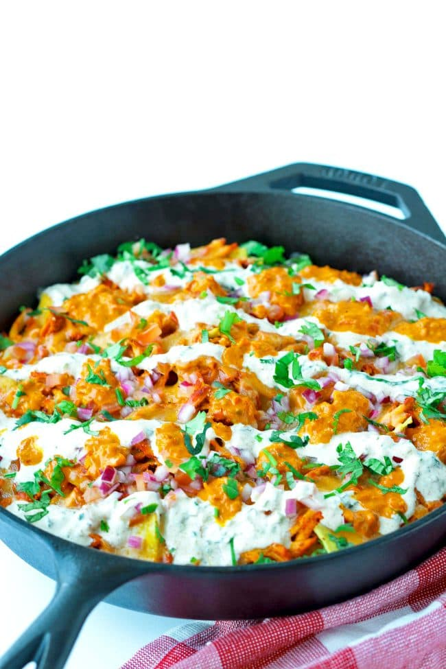 Front side view of cast iron skillet on red and white checkered patterned napkin with Chicken Tikka Nachos, topped with Creamy Cooling Yogurt Sauce and Red Chili sauce drizzled over the top. Garnished with freshly chopped coriander.