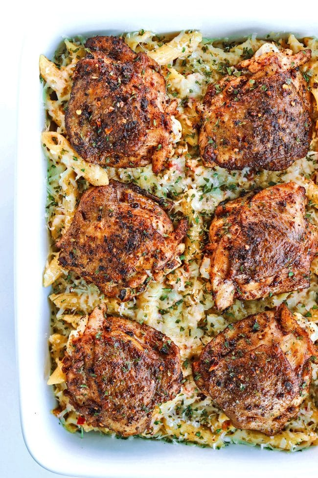 Overhead view of six grilled peri peri chicken thighs lined up on top of chili-lime cream sauce pasta in a 9x13 white baking dish.