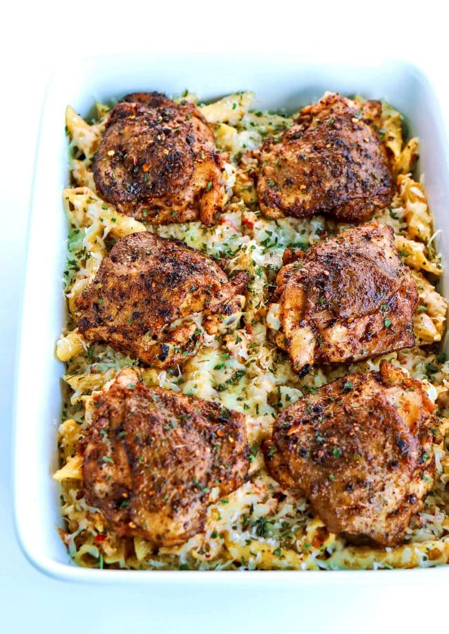 Front angle view of six grilled peri peri chicken thighs lined up on top of chili-lime cream sauce pasta in a 9x13 white baking dish.