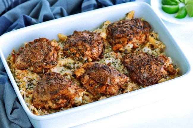 Diagonally placed 9x13 baking dish with Chili-Lime Cream Sauce Pasta with six grilled Peri Peri Chicken thighs on top. Dish is resting against a blue dinner napkin, a there's a small white plate of lime wedges to back right side.