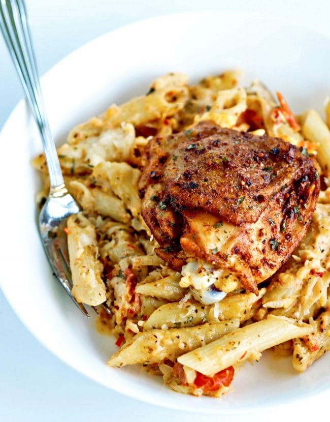 Deep white plate with a peri peri chicken grilled chicken thigh on top of a bed of chili-lime cream sauce penne pasta.
