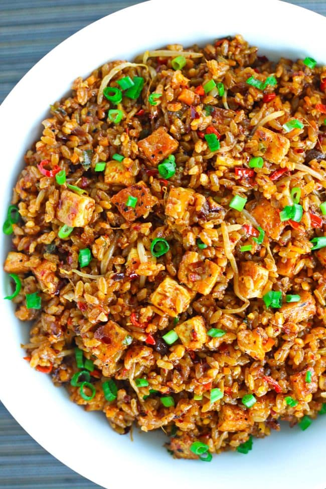 Top view of white serving bowl with Crispy Tofu Spicy Fried Rice, garnished with chopped spring onion on a brown oriental mat background.