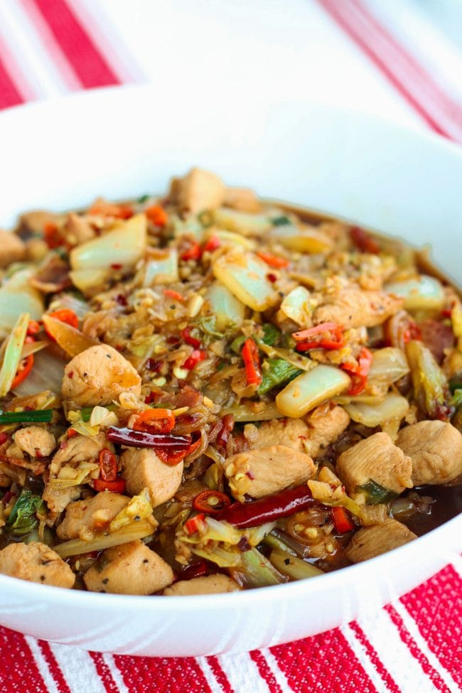 chicken, bacon, cabbage, spring onion, dried red chilies in white round serving bowl