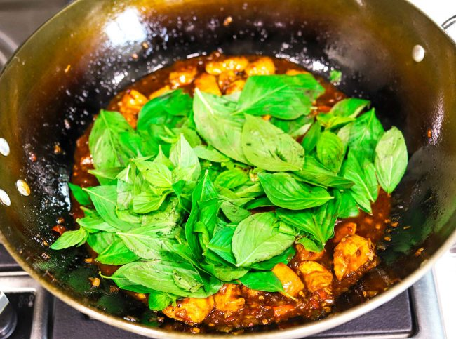 thai sweet basil leaves thrown on top of thai basil chicken that is cooking in a wok on the stovetop