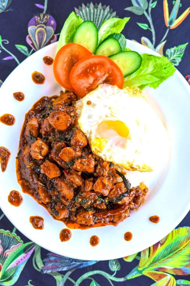 thai sweet basil chicken on a plate with white rice, cucumber slices, tomato slices, and lettuce. The rice is topped with a thai style fried egg. Background is a blue floral patterned napkin.