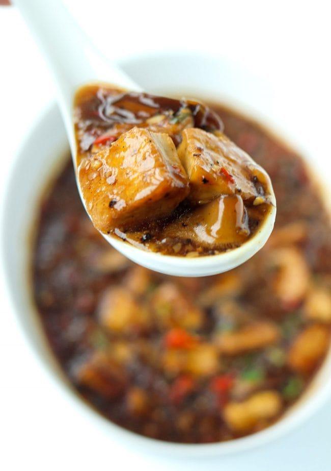black pepper sauce tofu cubes and mushrooms on spoon