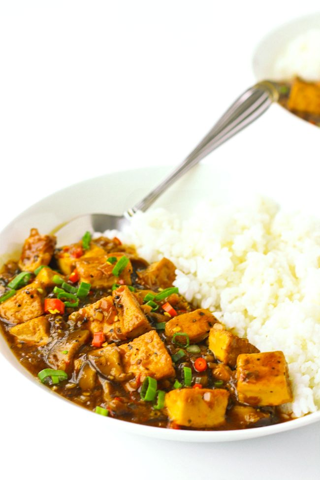 black pepper sauce tofu with spring onion garnish on plate with rice and spoon and