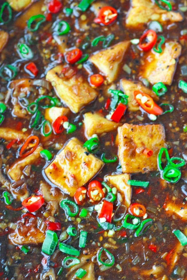 close up of black pepper sauce tofu cubes and mushrooms with spring onion and red chilies garnish