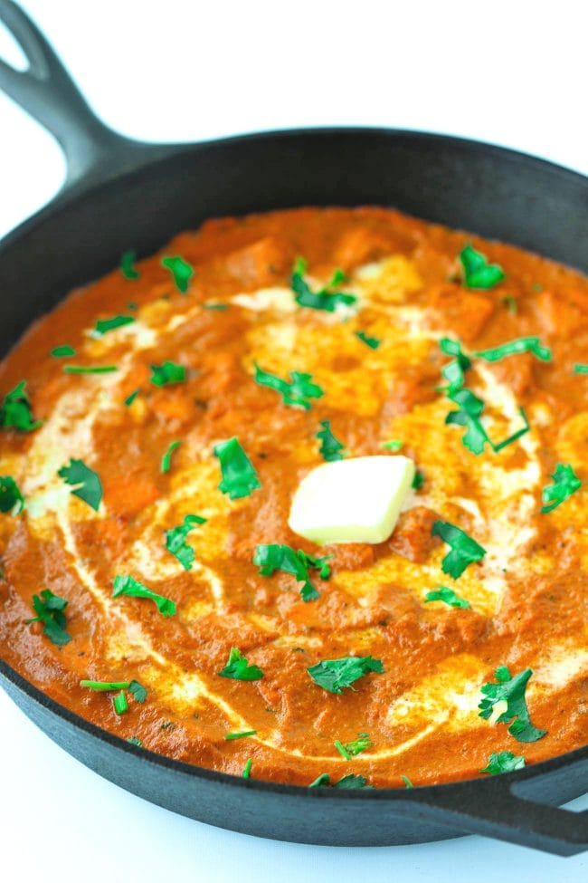 orange paneer curry garnished with coriander, cream, and butter in large black deep cast iron skillet.