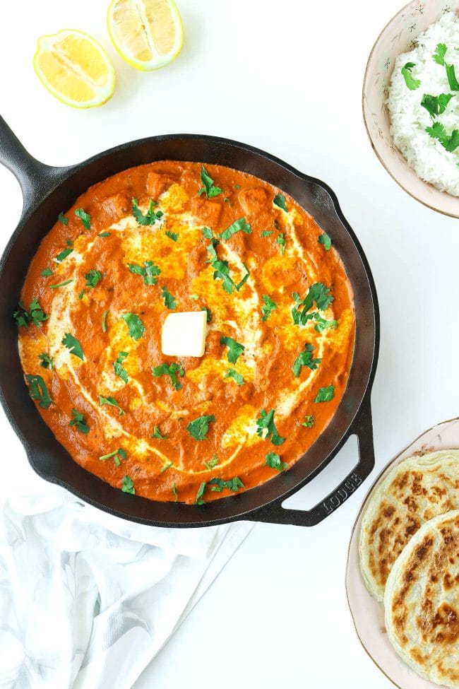 orange paneer curry in black skillet. Rice in a bowl and roti parathas on a plate next to skillet.