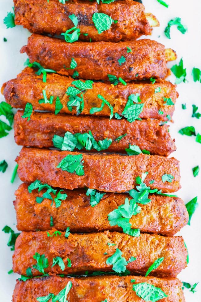tikka masala pork ribs on a white long plate garnished with coriander leaves