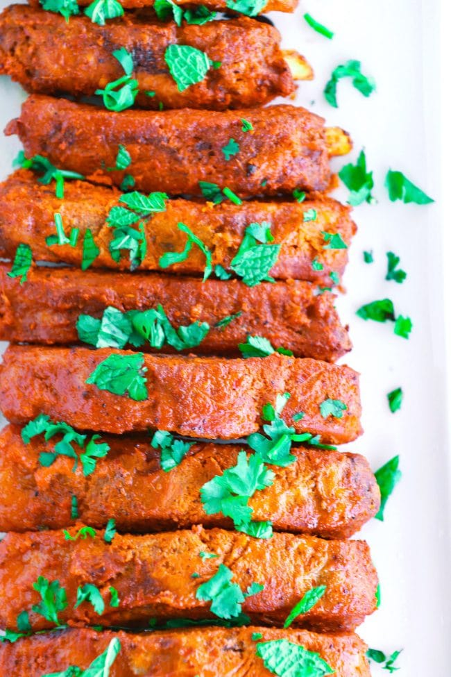 tikka masala pork ribs stacked on a white long plate garnished with coriander leaves