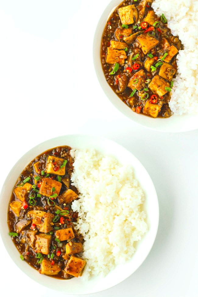 tofu in black pepper sauce on plate with rice and another plate of tofu and rice in the back