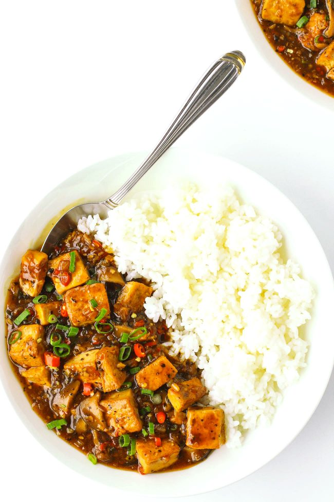 tofu in black pepper sauce on plate with rice and spoon