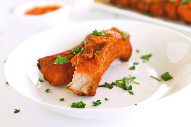 two orange pork ribs on a round plate with one that has a bite taken out of it
