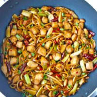 Chicken and noodles in a wok with dried red chilies, spring onion, and peanuts