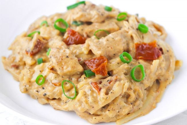creamy pasta with chicken on white round plate with spring onion and sundried tomato garnish