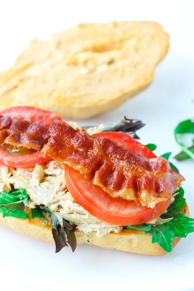 A chicken salad sandwich with spicy mayonnaise, tomato slices, mixed greens, and crispy bacon.