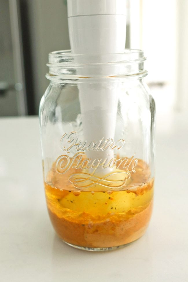 Handheld blender immersed in a jar and blending ingredients that are forming into a creamy mixture.