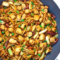 chicken, noodles, spring onion, garlic, ginger, dried red chilies, fresh red chilies, and peanuts in in a wok