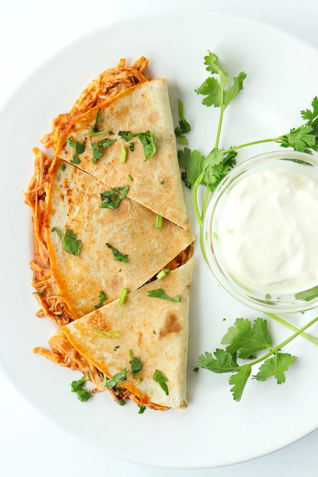 chicken quesadilla garnished with coriander and sour cream in a small dish on plate