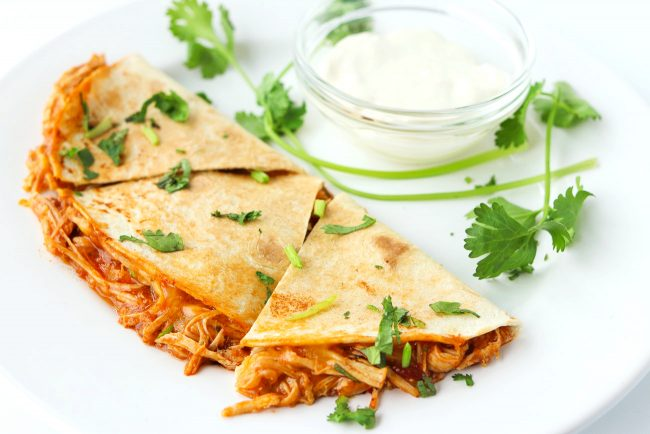 chicken quesadilla garnished with coriander and sour cream in a small dish on a plate