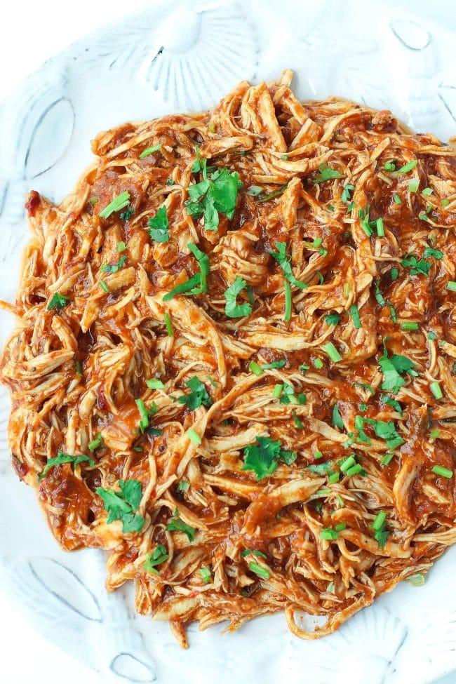 shredded salsa chicken garnished with coriander on plate