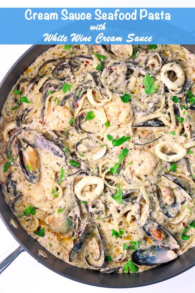 Cream Sauce Seafood Pasta with parsley garnish in a large deep sauté pan