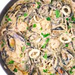 Pasta in a creamy white sauce with assorted seafood in a large deep sauté pan.