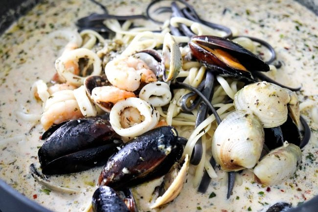 tossing linguini and seafood in white wine cream sauce