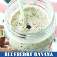 Hand holding up a mason jar mug with Blueberry Banana Smoothie and a straw.