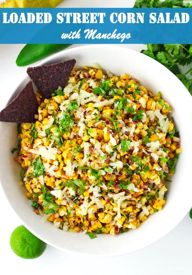 Corn salad in a bowl with two blue corn tortilla chips. Jalapeño, lime, and coriander bunch surrounding bowl.
