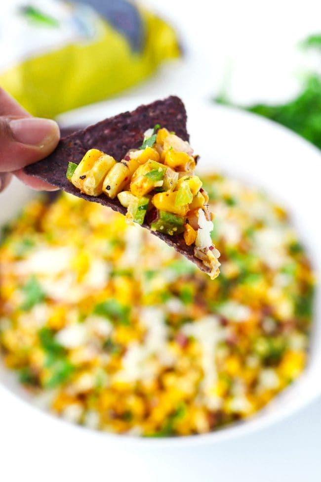 Fingers holding up a blue corn tortilla chip with some corn salad above a bowl filled with corn salad.