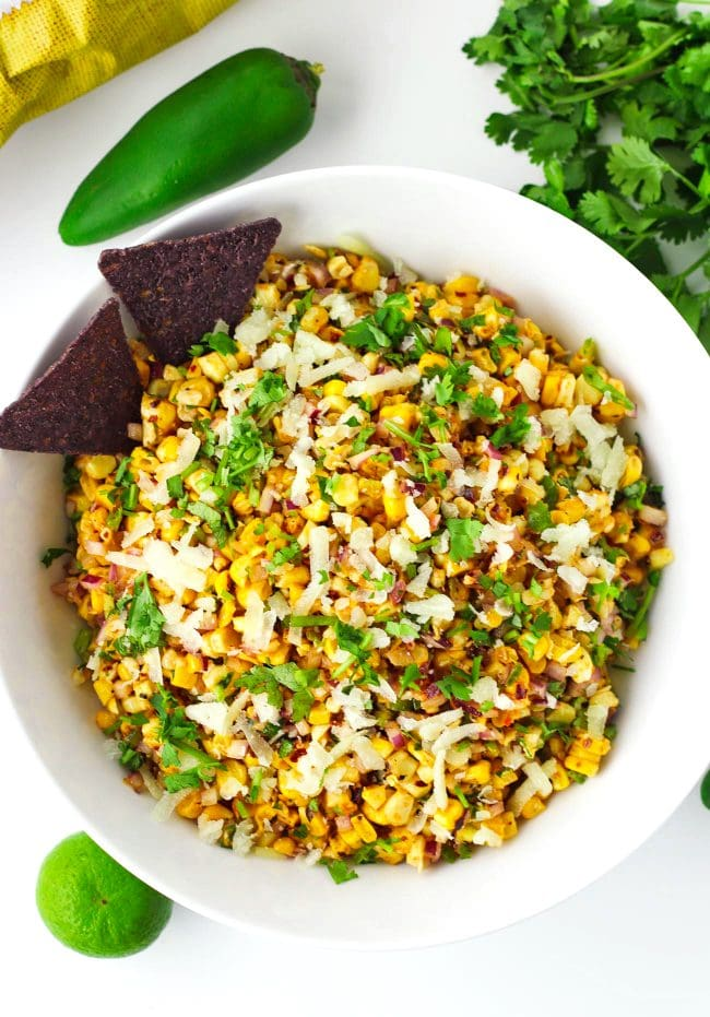 Corn salad garnished with cheese and coriander in a bowl with two blue corn tortilla chips. Jalapeño, lime, and coriander bunch surrounding bowl.