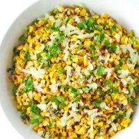 Corn salad in a white round bowl topped with grated cheese and coriander.
