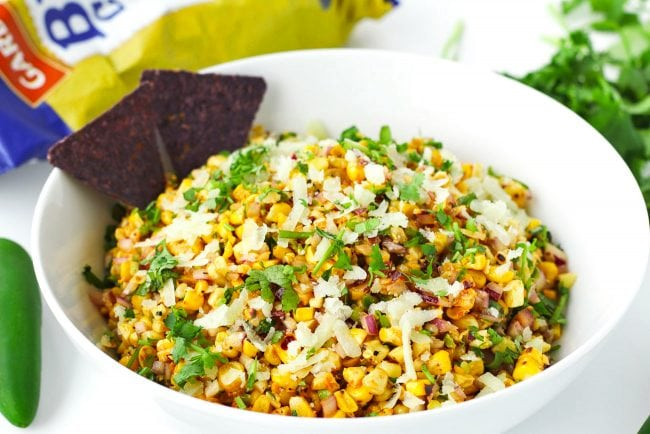 Corn salad in a serving bowl with two blue corn tortilla chips. A jalapeño, coriander bunch, and bag of tortilla chips surround the bowl.