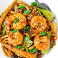 Asian stir-fry noodles with prawns, baby corn, mushrooms, bok choy, and spring onion garnish on a white plate with a fork.