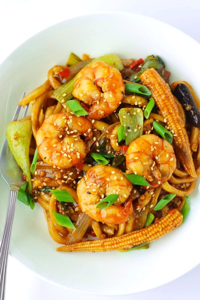 Stir-fry Sichuan Sauce Noodles with Jumbo prawns, baby corn, mushrooms, bok choy, and spring onion garnish on a white plate with a fork.