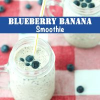 Two mason jar mugs with blueberry and banana smoothie with a straw in each mug. Blueberries scattered around the mug on a red and white checkered napkin.