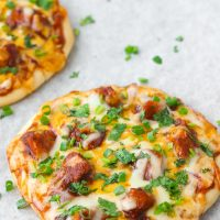 Two diagonally placed Spicy BBQ Chicken Pita Pizzas garnished with spring onion and chopped coriander
