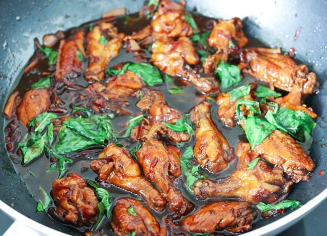 Three Cup Chicken in a wok with brown sauce and Thai sweet basil