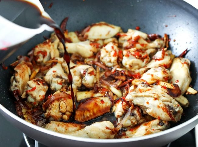 Pouring brown sauce over chicken and aromatics that are cooking in a wok on the stovetop.