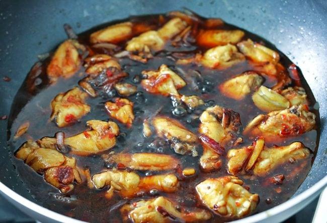 Three Cup Chicken in a wok simmering in dark brown sauce.